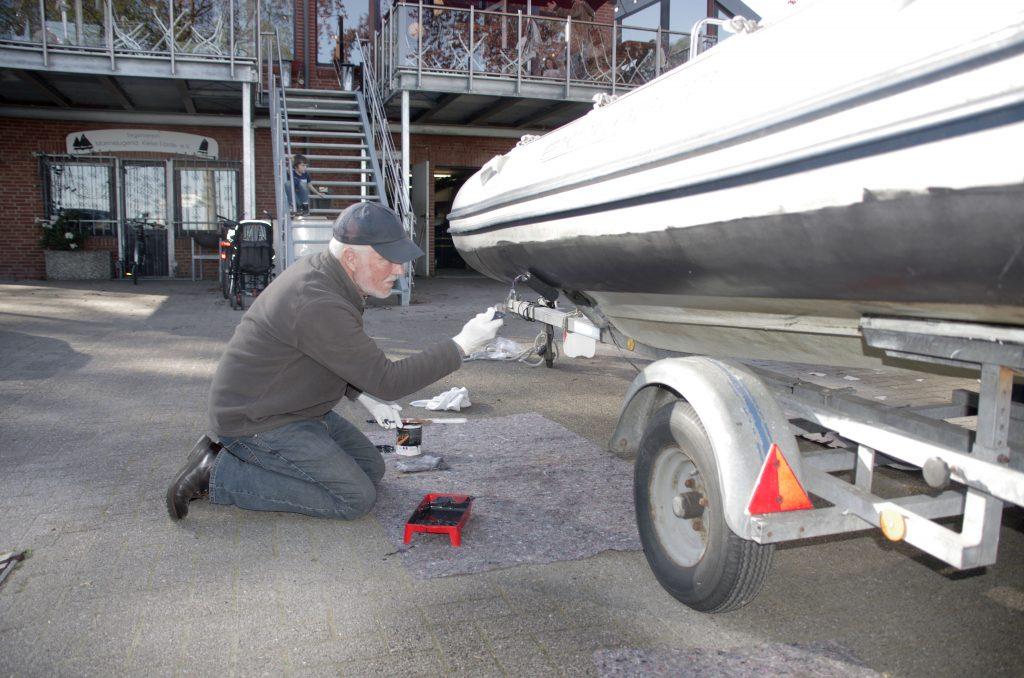 Dr. Dieter Hartwig trägt Antifouling beim großen Schlaufboot auf.